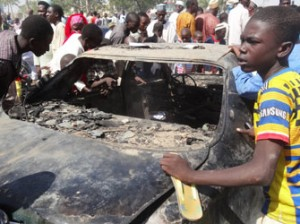 Residents look at a burnt car outside the central mosque in northern Nigeria's largest city of Kano on Novemer 29, 2014, a day after twin suicide blasts hit the mosque during weekly Friday prayers. At least 120 people were killed and 270 others wounded when two suicide bombers blew themselves up and gunmen opened fire during weekly prayers at the mosque, a week after the emir of Kano, Muhammad Sanusi II, of one of Nigeria's top Islamic leaders called on northerners to defend themselves against Boko Haram Islamists that have been carrying out deadly attacks and seizure of territory in the northeast. AFP PHOTO