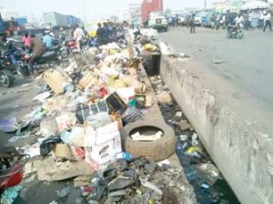 Heap of refuse at Coconut bus-stop on the Oshodi-Apapa expressway, yesterday.