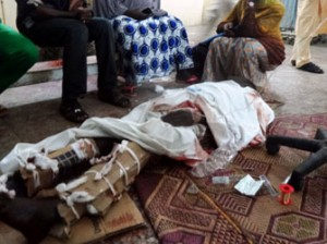 Relatives sit around one of the victims of twin suicide blasts at Kano central mosque in the accident and emergency ward of the Nassarawa Specilist Hospital in northern Nigeria's largest city of Kano on November 28, 2014. At least 120 people were killed and 270 others wounded when two suicide bombers blew themselves up and gunmen opened fire during weekly prayers at the mosque, a week after the emir of Kano, Muhammad Sanusi II, of one of Nigeria's top Islamic leaders called on northerners to defend themselves against Boko Haram Islamists tha have been carrying deadly attacks and seizure of territory in the northeast. AFP PHOTO