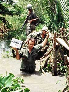 *Don North, war correspondent in Vietnam for ABC News, crosses a stream in the Mekong Delta, 1968