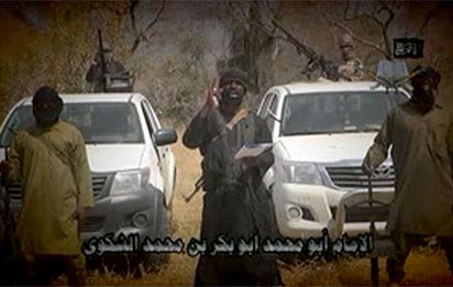 "In this screen grab image taken on February 9, 2015 from a video made available by Islamist group Boko Haram, leader Abubakar Shekau (C) makes a statement at an undisclosed location.  Boko Haram leader Abubakar Shekau vowed in a new video released on January 9, 2015 that the group would defeat a regional force fighting the militants in Nigeria's far northeast, Niger and Cameroon.""AFP PHOTO / BOKO HARAM"" -"