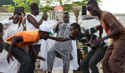 Young men dance in front of a makeshift figure of former military ruler and presidential candidate Muhammadu Buhari in Kaduna, which was hit hard by interreligious violence during the 2011 election, on March 29, 2015. Nigeria counted ballots in its closely fought general election after failures in controversial new technology pushed voting into a second day, with officials calling for calm in the tense wait for a winner. AFP PHOTO