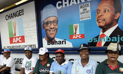 """Women sit in a branded bus station as they support leading opposition All Progressives Congress presidential candidate Mohammadu Buhari during a rally christened 'Walk for Change"""" in Lagos, on March 7, 2015 in Lagos, Nigeria's commercial capital.  Presidential elections scheduled for February 14 were delayed for six weeks as the military said the ongoing counter-offensive against Islamists Boko Haram meant that troops could not provide security on polling day. Elections will take place on March 28, with gubernatorial and state house assembly polls two weeks later.  AFP PHOTO"""
