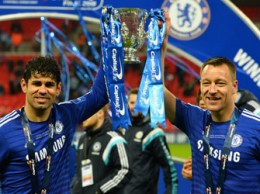 """Goalscorers Chelsea's Brazilian-born Spanish striker Diego Costa and Chelsea's English defender John Terry (R) celebrate with the trophy during the presentation after Chelsea won the League Cup final football match against Tottenham Hotspur at Wembley Stadium in London on March 1, 2015. Chelsea won 2-0. AFP PHOTO / GLYN KIRK  RESTRICTED TO EDITORIAL USE. No use with unauthorized audio, video, data, fixture lists, club/league logos or """"live"""" services. Online in-match use limited to 45 images, no video emulation. No use in betting, games or single club/league"""