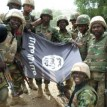 A handout picture from the Nigerian military taken on February 26, 2015 shows troops posing with a flag of Boko Haram after dismantling a Boko Haram camp along Djimitillo Damaturu road, Yobe State in northeastern Nigeria, following fierce fighting that resulted in the capture of machine guns and rifles as well as the death of a number of the insurgents. Boko Haram has vowed to disrupt March 28 elections, which originally were planned for February 28 but rescheduled following security threat. AFP