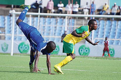 STUMBLE: Shooting Stars Adeyinka Adedeji(l) stumbles during a GLO Premier League match between Shooting Stars Sports Club of Ibadan and Kano  Pillars in Ibadan yesterday. 3SC won 1-0. Photo courtesy LMC Media