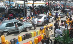 THE AGONY CONTINUES —The crowd and long queues of jerry cans at Capital Oil filling station, along Lagos-Ibadan Expressway, yesterday. Below right: Stranded commuters' option B in Lagos, also yesterday. Photos:Lamidi Bamidele with NAN.