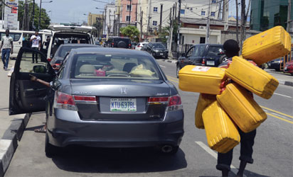A man carries jerrycans to search for fuel in Lagos, on May 21, 2015. Long queues formed at petrol stations across oil-rich Nigeria on May 21 following a row over subsidy payment to petrol importers as well as sale of government oil blocks to private investors, union officials said. AFP PHOTO