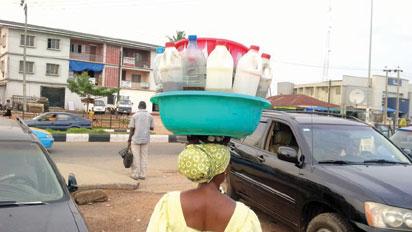 A woman hawking Ogogoro drinks in Akure
