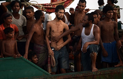 Rohingya migrants sit and stand on a boat drifting in Thai waters off the southern island of Koh Lipe in the Andaman sea on May 14, 2015.  A boat crammed with scores of Rohingya migrants -- including many young children -- was found drifting in Thai waters on May 14, with passengers saying several people had died over the last few days.   AFP PHOTO / Christophe ARCHAMBAULT