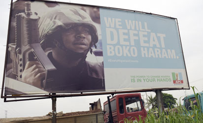 """A photo shows a campaign signboad displayed by the ruling All Progressives Congress (APC) to show its readiness to defeat Boko Haram Islamists on assumption office at Ogijo, Ogun State in southwest Nigeria, on July 3, 2015. Boko Haram carried out a fresh wave of massacres in northeastern Nigeria on July 3, locals said, killing nearly 200 people in 48 hours of violence President Muhammadu Buhari blasted as """"inhuman and barbaric"""". AFP PHOTO"""