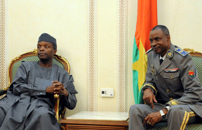 Nigeria's Vice-President Yemi Osinbajo (L) is welcomed by Bukina Faso's coup leader General Gilbert Diendere (R), on September 23, 2015 at Ouagadougou International airport as six leaders of the Economic Community of West African States (ECOWAS) arrive to oversee the formal re-installation of interim President Michel Kafando and to try and sort out two contentious issues : an amnesty plan for the putschists and whether upcoming elections should be open to supporters of previously deposed veteran dictator Blaise Compaore. Burkina Faso's Kafando said he has resumed his duties a week after being overthrown in a coup by the west African country's presidential guard. AFP PHOTO / AHMED OUOBA