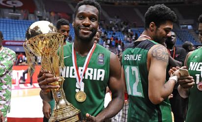 Nigerian Basketball star, Chamberlain Oguchi displays the Afrobasket championship trophy.