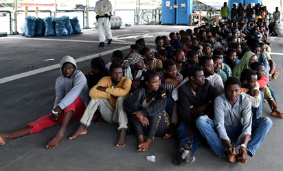 Over 140 migrants and refugees, mainly from Nigeria, Ghana, Senegal and Sierra Leone who were transported by the German navy frigate Werra as part of the European external action service EU Navfor Med, wait to disembark at the Augusta harbour in eastern Italy on September 27, 2015. Some 500 migrants were rescued in seven operations launched over the weekend in the Mediterranean, the Italian coastguard said. The EU Navfor Med is a military operation launched at the end of June to identify, capture and dispose of vessels and rescue migrants undertaking risky journeys in a desperate bid to try and get to Europe from war-ravaged Syria and other trouble spots. AFP PHOTO
