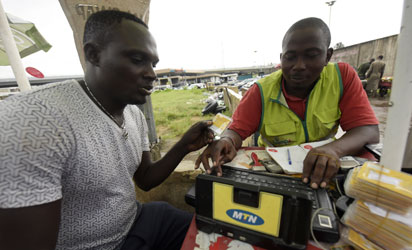 A MTN service provider tries to register a client's SIM card in Lagos, on October 27, 2015.  Nigeria's telecommunications regulator has fined South African mobile giant MTN $5.2 billion for missing a deadline to disconnect unregistered SIM cards, the company announced on Monday. The penalty saw shares in Africa's largest telecommunications company crash more than 12 percent to 167 rand on the Johannesburg Stock Exchange, the biggest fall the firm has suffered in a day since November 1998. AFP PHOTO