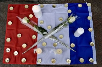 Candles and white roses are displayed on the French flag in  Toulouse on November 14, 2015 as a tribute to the victims of the attacks in Paris in which 128 people were killed.  Islamic State jihadists on Saturday claimed a series of coordinated attacks by gunmen and suicide bombers in Paris that killed at least 128 people in scenes of carnage at a concert hall, restaurants and the national stadium.  AFP