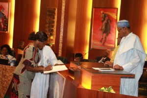 INEC National Commissioner, Prof. Antonia Okoosi-Simbine signing the oath book before President Muhammadu Buhari during the swear-in ceremony of INEC Chairman and five National Commissioners at the Aso Chambers, State House, Abuja. Photo by Abayomi Adeshida 09/11/2015