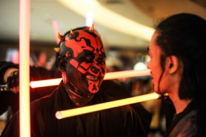 A member of Malaysia's Star Wars Fan Club dressed as Darth Maul (C) attends a viewing of 'Star Wars: The Force Awakens' at a cinema in Subang, outside Kuala Lumpur on December 17, 2015. AFP PHOTO / MOHD RASFAN