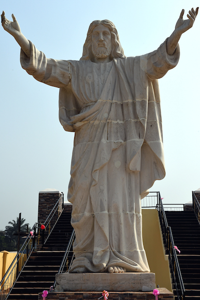 """A picture taken on January 1, 2016 shows the nine-metre tall statue of Jesus Christ carved from white marble, thought to be the biggest of its kind in Africa, unveiled in Abajah, southeastern Nigeria. Standing barefoot with arms outstretched, the """"Jesus de Greatest"""" statue weighs in at 40 tonnes. More than 100 priests and hundreds of Catholic worshippers attended the nine-metre (30-foot) statue's official unveiling in the village of Abajah in southeastern Nigeria. It was commissioned by Obinna Onuoha, a local businessman who hired a Chinese company to carve it and placed it in the grounds of a 2000-capacity church that he built in 2012. / AFP / PIUS UTOMI EKPEI"""