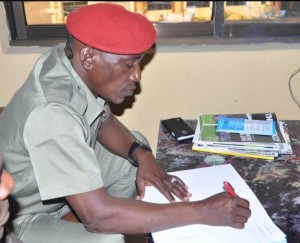 Minister of Youth and Sports, Solomon Dalung signing the condolence register of NFF, Head of Protocol, Ibrahim Abubakar, at NFF Secretariat, Abuja, on Wednesday, January 6, 2015