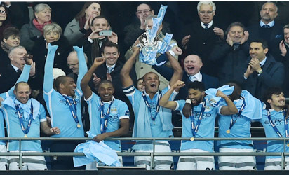 Manchester City's Belgian defender Vincent Kompany (C) holds up the English League Cup during the presentation after Manchester City won the English League Cup final football match between Liverpool and Manchester City at Wembley Stadium in London on February 28, 2016. / AFP