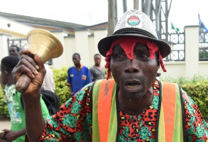 """A worker rings a bell during a protest demanding that the government reinstate prices of fuel at 86.50 naira ($0.43, 0.38 euros) per litre in Lagos, on May 18, 2016. Nigeria's government on May 18 warned against """"illegal strike action"""" after some union members vowed to press ahead with a national strike over petrol price rises despite a court injunction."""