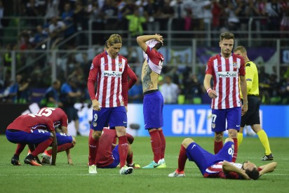 Atletico Madrid players look dejected after they lost the UEFA Champions League final football match to Real Madrid at San Siro Stadium in Milan, on May 28, 2016. / AFP PHOTO / OLIVIER MORIN