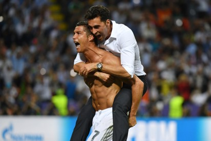 Real Madrid's Portuguese forward Cristiano Ronaldo (L) celebrates with a member of staff after Real Madrid won the UEFA Champions League final football match over Atletico Madrid at San Siro Stadium in Milan, on May 28, 2016. / AFP PHOTO / GERARD JULIEN