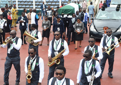 Musicians play brass instruments as pallbearers carry the coffin of former Nigerian football coach Stephen Keshi during a farewell ceremony at the Ogbe Stadium, in Benin City, on July 28, 2016.  Nigerian football legend Stephen Keshi, who died aged 54, was a Cup of Nations winner as a player and coach. Supporters and international football players gathered to bid farewell, at the Ogbe Stadium, in Benin, on the eve of his funeral in his hometown Illah. / AFP PHOTO / PIUS UTOMI EKPEI