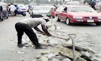 Man of God filling pot-holes along Imgbi road, Yenagoa metropolis