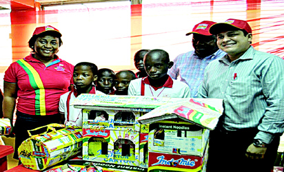 """L-R: Coordinator, Indomie Fans Club, Mrs. Faith Joshua; pupils of Great God Academy, Ogun State; Group Public Relations And Events Manager, Dufil Prima Foods Plc, Mr. Tope Ashiwaju; and Marketing Director, Dufil Prima Foods Plc, Girish Sharma, at the Indomie """"Team Yourself Up"""" competition in Lagos."""