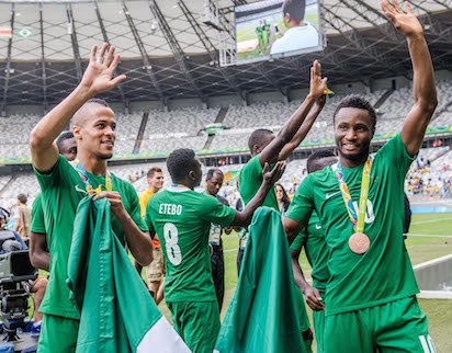 Nigeria's players William Ekong (L) and John Obi Mikel (R) celebrate after receiving their bronze medals during the medal ceremony after defeating Honduras in the Rio 2016 Olympic Games men's bronze medal football match at the Mineirao stadium in Belo Horizonte, Brazil, on August 20, 2016.  / AFP PHOTO / GUSTAVO ANDRADE