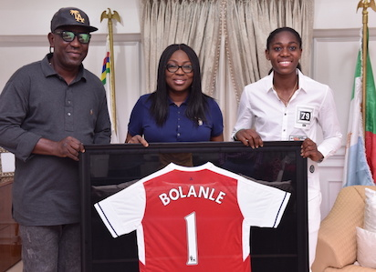 Wife of Lagos State Governor, Mrs. Bolanle Ambode (middle), being presented with an Arsenal Football Club jersey by Super Falcons and Arsenal Ladies FC star, Azeezat Oshoala (right) during Oshoala's courtesy visit to the Wife of the Governor, at Lagos House, Ikeja, on Friday, August 12, 2016. With them is Senior Special Assistant on Sport to the Governor, Mr. Anthony Adeyinka Adeboye (left).