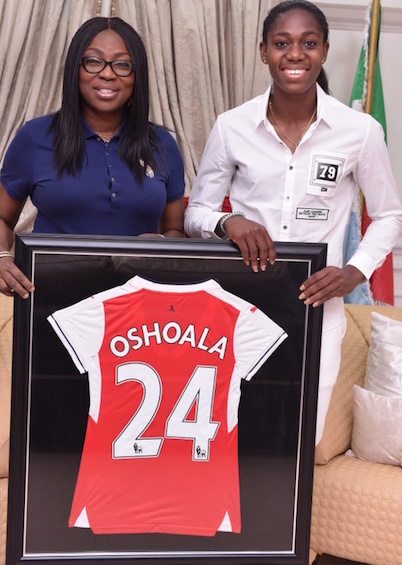Wife of Lagos State Governor, Mrs. Bolanle Ambode (right), being presented with an Arsenal Football Club jersey by Super Falcons and Arsenal Ladies FC Star, Azeezat Oshoala (left) during Oshoala's courtesy visit to the Wife of the Governor, at Lagos House, Ikeja, on Friday, August 12, 2016.