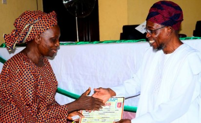 One of the 266 retirees from the Osun state civil service receiving her Retirement Bond Certificate from Governor Rauf Aregbesola