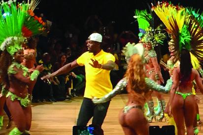 SAMBA DANCE.......Usain Bolt (C) dances samba with  scantily-clad dancers