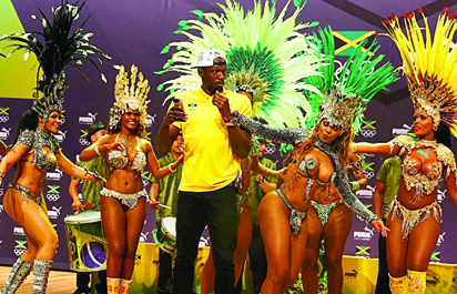 SO GOOD TO BE TRUE.....Jamaican track star, Usain Bolt soaks in the fun as Brazilian dancers wriggle their waits during a show at the Rio Games
