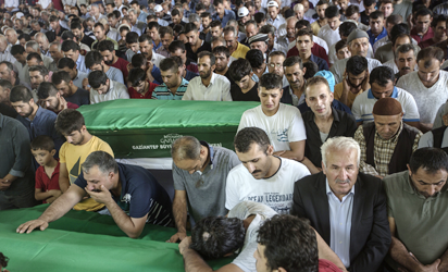 "People react as they stand around coffins during a funeral for victims of last night's attack on a wedding party that left 50 dead in Gaziantep in southeastern Turkey near the Syrian border on August 21, 2016. At least 50 people were killed when a suspected suicide bomber linked to Islamic State jihadists attacked a wedding thronged with guests, officials said on August 21. Turkish President Recep Tayyip Erdogan said the IS extremist group was the ""likely perpetrator"" of the bomb attack, the deadliest in 2016, in Gaziantep late Saturday that targeted a celebration attended by many Kurds. AFP PHOTO"