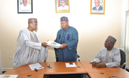 Senator Magoro, left,  presents the report to the Vice chairman, North West, Inuwa Abdul-Kadir