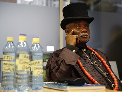 Bottled water samples stand on a table as Nigerian tribal king Emere Godwin Bebe Okpabi speaks during an interview in central London on November 21, 2016. Britain's High Court will on November 22, begin to hear arguments on whether the English Courts can hear two legal claims on behalf of over 40,000 Nigerians against Royal Dutch Shell and its Nigerian subsidiary, Shell Petroleum Development Company of Nigeria (SPDC), in relation to environmental damage caused to two separate communities in the Niger Delta. / AFP PHOTO