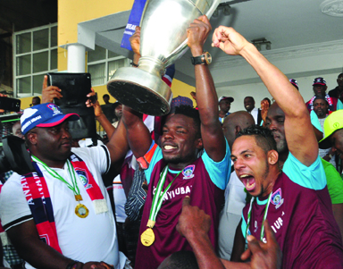UP CHAMPS! ...Dr Ifeanyi Ubah, Charmian FC Ifeanyiubah ( L)  Elu Wilson Team Captain FC Ifeanyiubah and Alberico Da Silva lifting the 2016 Federation Cup trophy after beating Nasarawa United 5-4 via penalty shoot out. .Photo: Akeem Salau