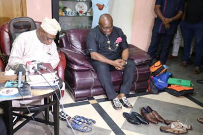 Obasanjo (left) with Ikpeazu admiring the shoes.