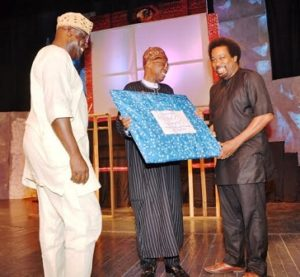 """Minister of Information and Culture Lai Mohammed (Middle) receiving a souvenir from Makin Soyinka during the Command Performance of ''Death and the King's Horseman"""" in Lagos on Saturday to commemorate the 30th anniversary of the award of Nobel Prize to Prof. Wole Soyinka.   Artistic Director of the National Troue Akin Adejuwon (Left) looks on"""