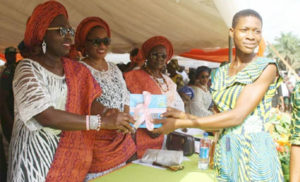 Wife of Ondo state Governor, Chief (Mrs) Betty Anyanwu - Akeredolu (left), presenting Certificate to one of the beneficiaries (right); Commissioner for Women Affairs and Social Development, Hon. Omowunmi Olatunji Edet (second left) at the Forum for Wives of Ondo State Officials, (FOWOSO) Empowerment Outreach Programme for Women, Youths and Special needs people in Akoko South West Local Government Area of Ondo State.