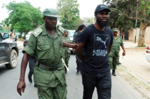Zambian musician Chama Fumba, known as Pilato, is led away by police after protest.